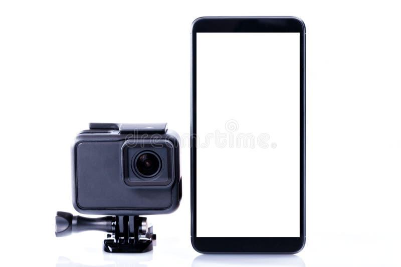 Uma câmera video moderna dos esportes ao lado de um smartphone preto com a tela em vazio isolada foto de stock