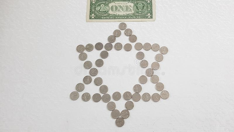 Uma cédula americana do dólar colocada sobre as moedas israelitas do metal do shekel arranjadas em uma forma de seis pontos judai imagem de stock royalty free