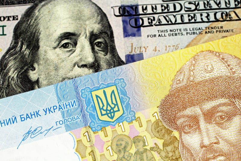 Uma cédula um ucraniano do hryvnia com umas cem notas de dólar americana foto de stock royalty free