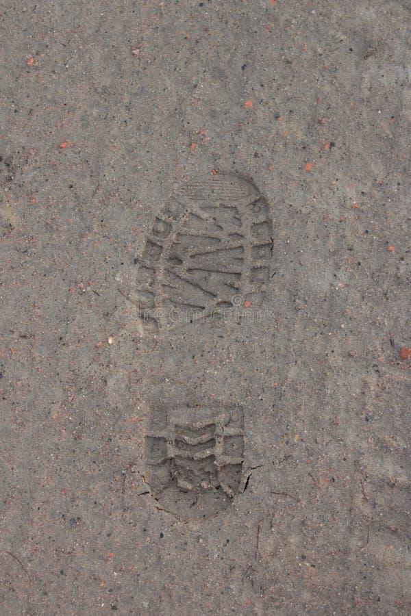Uma cópia da bota na areia imagem de stock