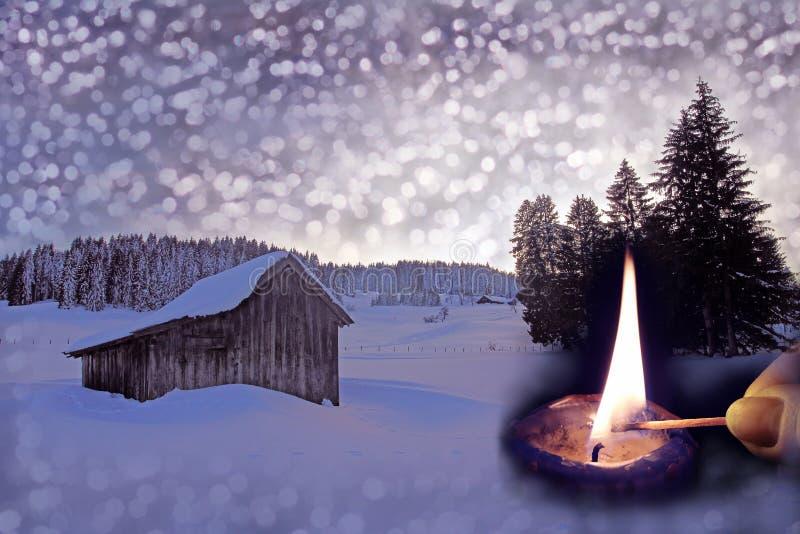 Uma cabana de madeira velha na neve com flocos de neve do Natal, ramos do abeto e uma vela ardente fotografia de stock royalty free