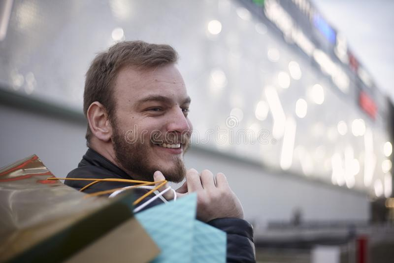 uma cabeça da cara do homem novo, 20-29 anos velha, olhando lateralmente Sacos de compras levando em suas mãos fotografia de stock royalty free