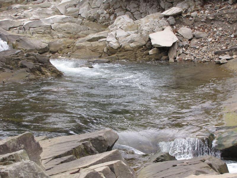 Uma cachoeira pequena em um rio da montanha imagem de stock