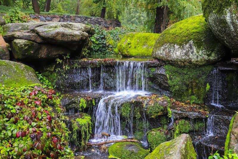 Uma cachoeira pitoresca da cascata entre o grande musgo cobriu pedras na paisagem Sophia Park, Uman, Ucrânia, outono imagens de stock royalty free