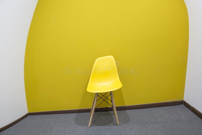 Uma cadeira amarela com a parede amarela na sala de reunião fotografia de stock royalty free
