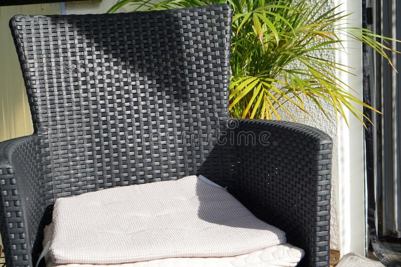 Uma cadeira com os coxins de assento exteriores no jardim ou no balcão na frente de uma planta verde imagem de stock