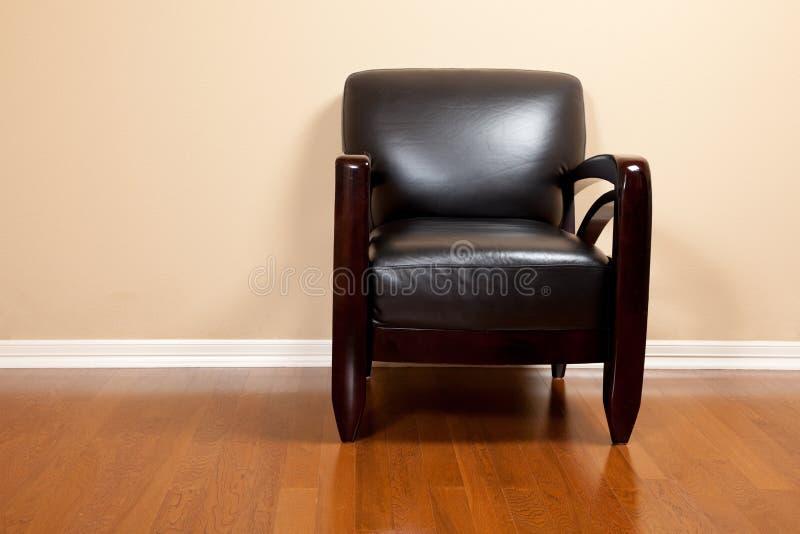 Uma cadeira de couro preta vazia na casa imagens de stock royalty free