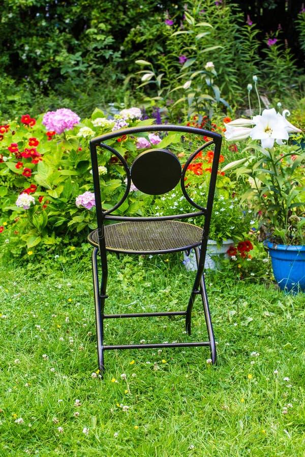 Uma cadeira de jardim no jardim do verão fotos de stock royalty free