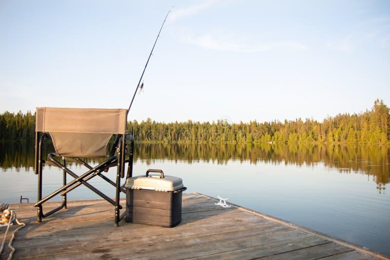 Uma cadeira em uma doca de madeira que olha para fora em um lago no verão com equipamento de pesca imagens de stock royalty free