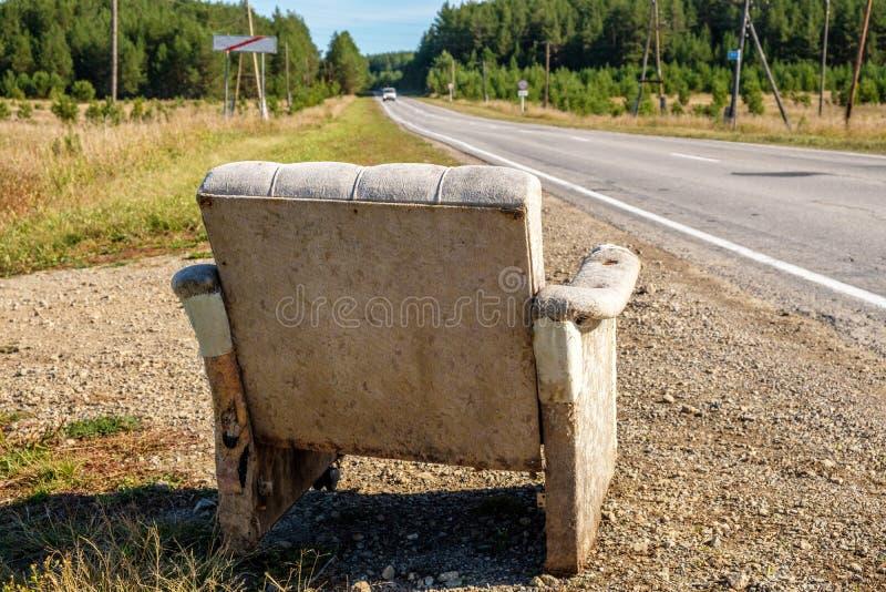 Uma cadeira que espera passando carros, estofada uma cadeira velha está no lado da estrada foto de stock royalty free