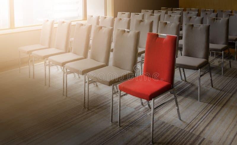 Uma cadeira vermelha diferente de outro na sala de conferências vazia fotos de stock royalty free