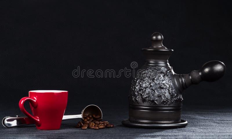 Uma cafeteira, um copo e uma colher de medição de aço com feijões de café imagens de stock royalty free