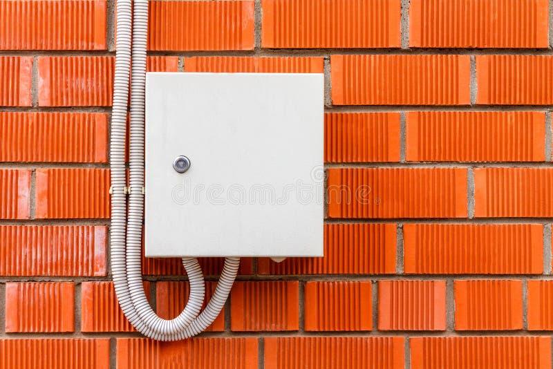 Uma caixa branca com um cabo de alta tensão bonde em um tijolo vermelho w imagem de stock