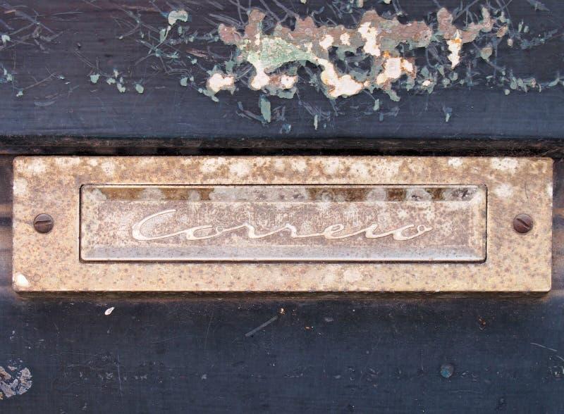uma caixa de letra de oxida??o velha do cromo em uma porta de madeira azul com pintura de descascamento lascada com o correio da  imagem de stock