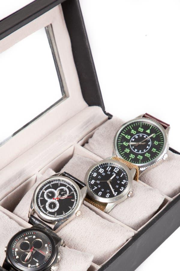 Uma caixa de presente preta aberta com os relógios luxuosos isolados no fundo branco foto de stock