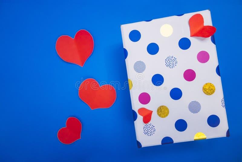 Uma caixa pequena de mentiras coloridas das ervilhas ao lado dos corações vermelhos imagem de stock