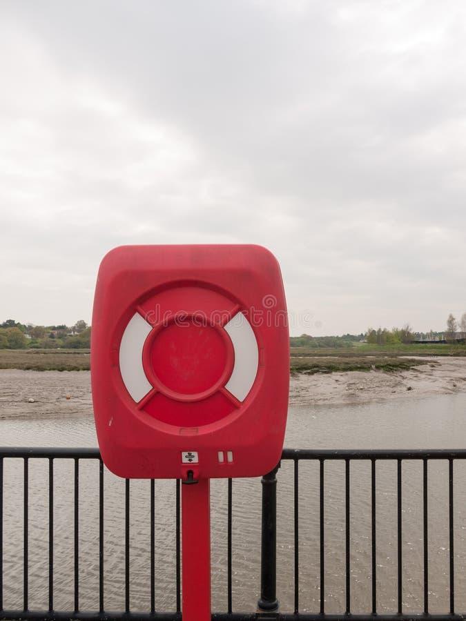 Uma caixa vermelha e branca fechado da boia da segurança na frente marítima d do beira-mar fotografia de stock