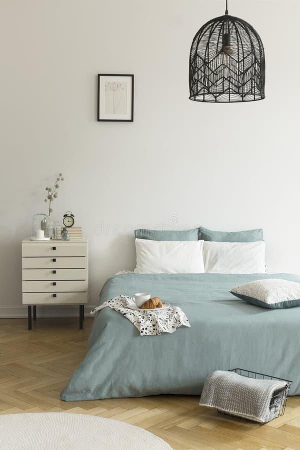 Uma cama de casal com o fundamento do verde prudente e do branco que está em um assoalho de madeira em um interior brilhante do q foto de stock