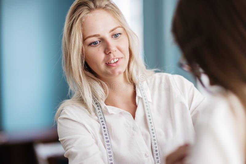 Uma camisa branca vestindo devista da mulher loura bonita está sorrindo com uma fita-linha no pescoço Forma, alfaiate imagens de stock