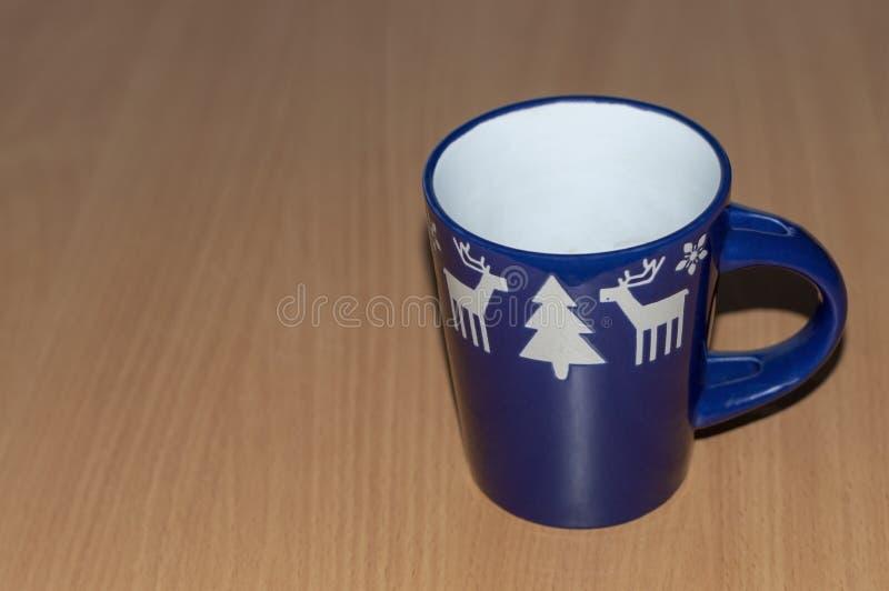 Uma caneca azul vazia com um punho com cervos, árvores de Natal foto de stock