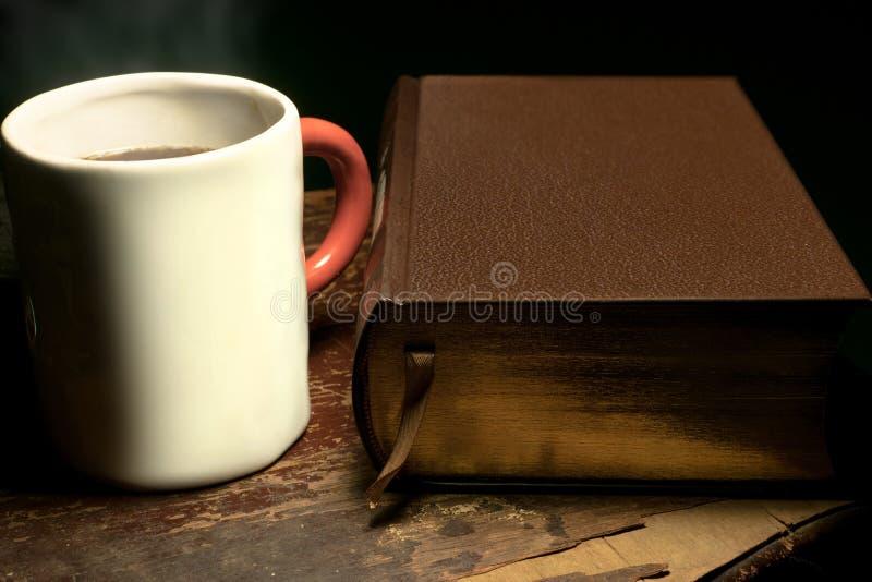 Uma caneca com cozinhar o chá ou o café quente colocado ao lado de um livro grande do couro-limite, em uma tabela de madeira velh fotos de stock royalty free