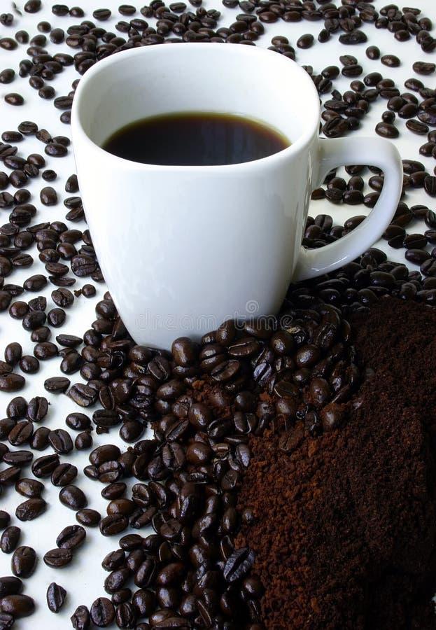 Uma caneca de café cercada por feijões de café fotografia de stock royalty free