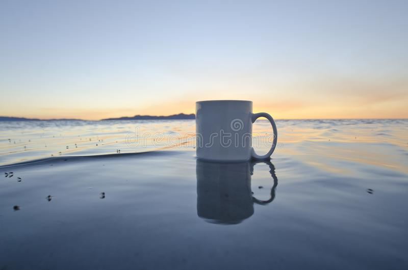 Uma caneca de café vazia de solo na água de Great Salt Lake fotos de stock