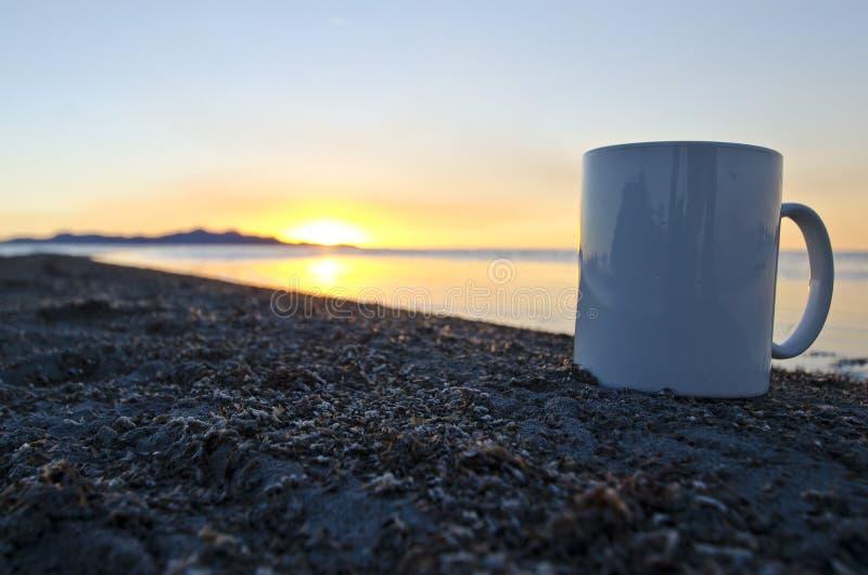 Uma caneca de café vazia de solo no erro encheu a linha costeira imagens de stock