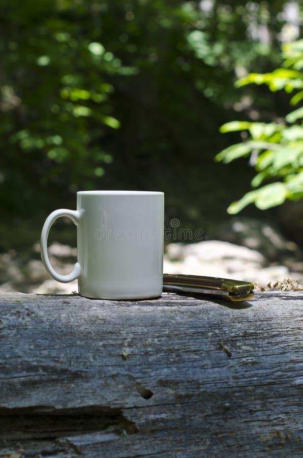 Uma caneca vazia e uma faca dobrada fotografia de stock
