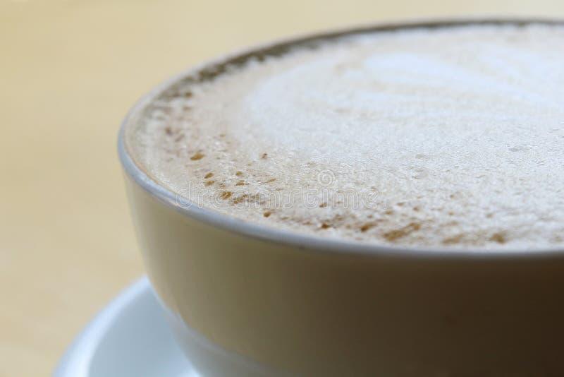 Uma x?cara de caf? com teste padr?o do cora??o em um copo branco no fundo de madeira imagem de stock royalty free
