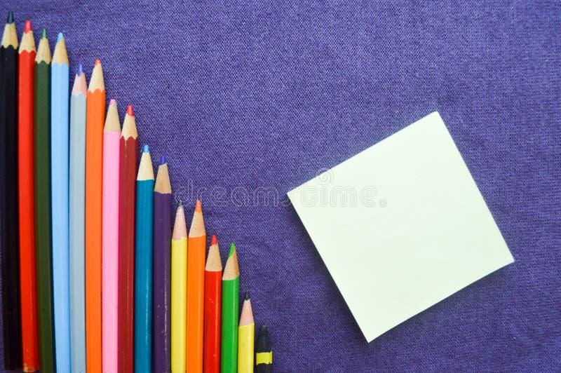 Uma carta descendente de lápis de tiragem coloridos, brilhantes, variegated, um caderno fotografia de stock