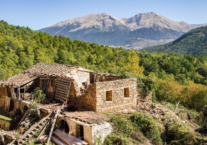 Uma casa abandonada velha para fora de inclinação arruinada na montanha em Grécia fotos de stock
