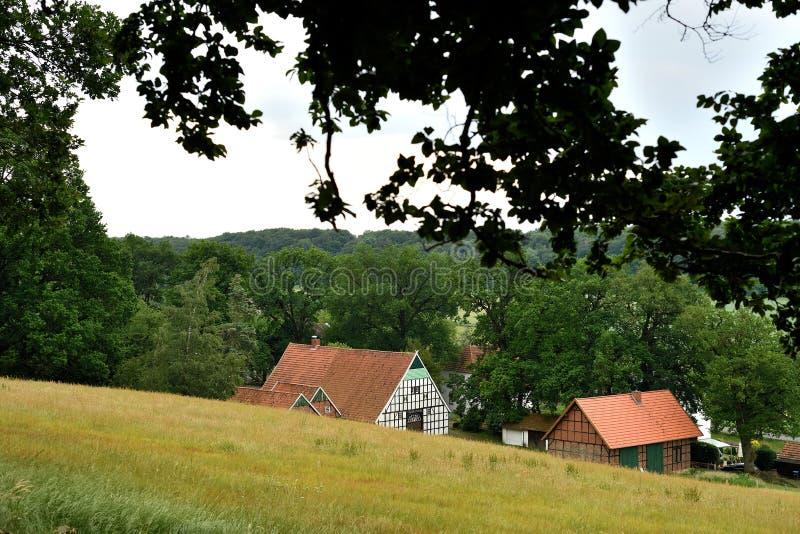 Uma casa alemão típica da exploração agrícola do fachwerk na inclinação sul da montanha de Tecklenburger fotos de stock royalty free