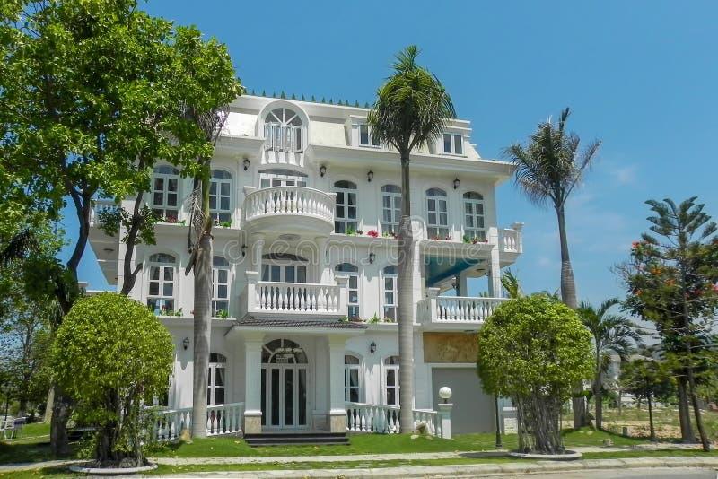 Uma casa bonita da quatro-história com palmeiras, árvores, e projeto da paisagem no verão fotos de stock