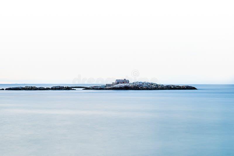 Uma casa constru?da em uma ilha rochosa pequena no meio do mar fotografia de stock royalty free