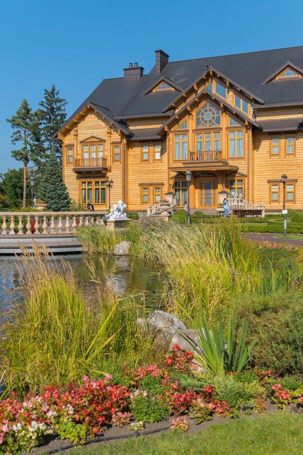 Uma casa de madeira com balcões em um parque bonito perto de um lago artificialmente criado fotos de stock