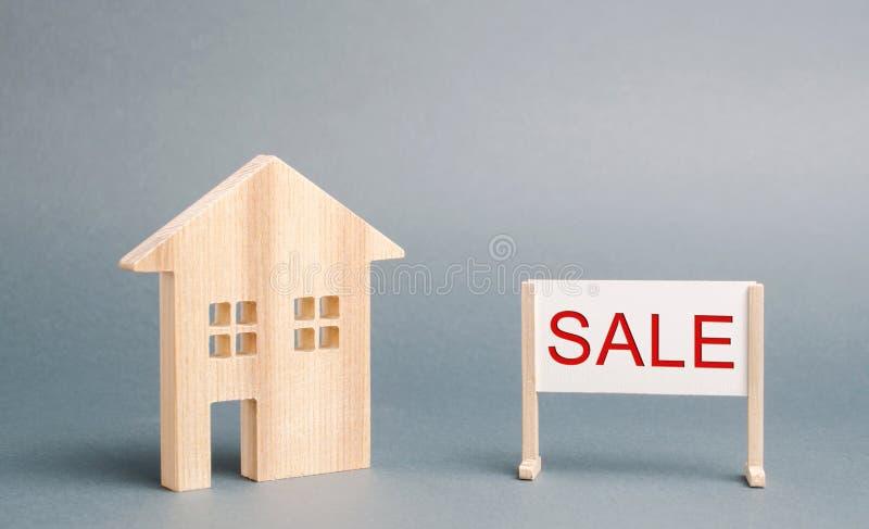 Uma casa de madeira diminuta e um cartaz com a venda da palavra O conceito de vender uma casa ou um apartamento Propriedade para  foto de stock