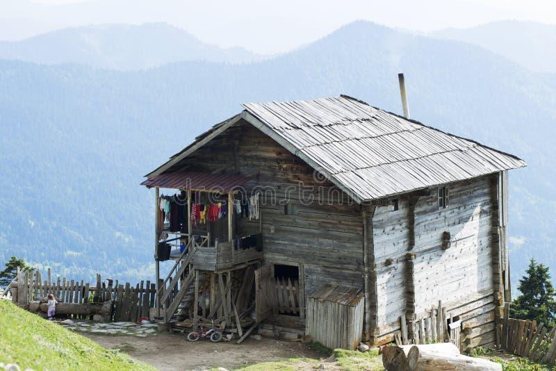 Uma casa de madeira velha autêntica em um Highland Village entre cordilheiras infinitas fotos de stock royalty free