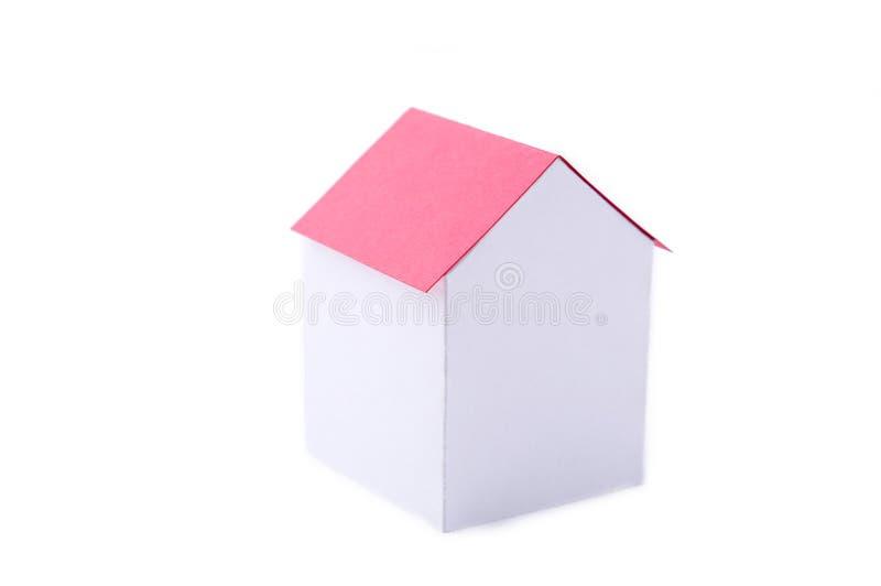 Uma casa de papel com telhado vermelho em um fundo branco fotos de stock
