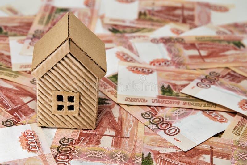 Uma casa do cartão e muito valor do dinheiro cinco mil rublos imagens de stock royalty free
