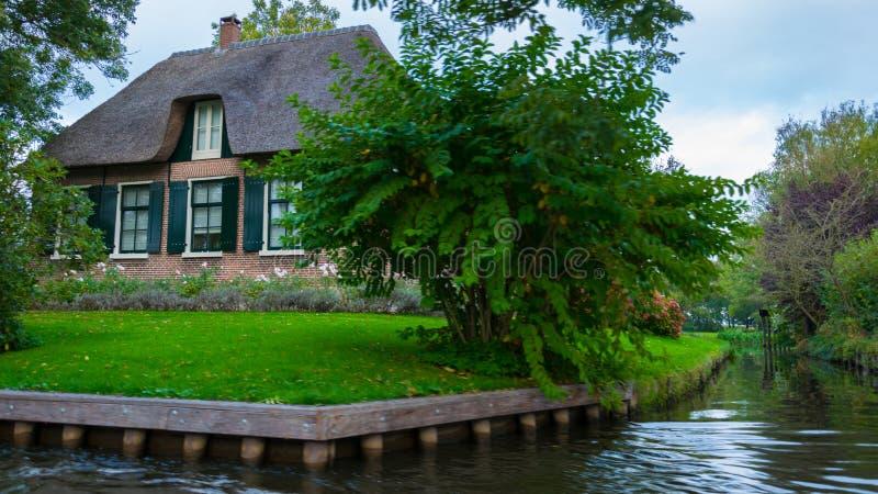 Uma casa em Giethoorn, nos Países Baixos, fotografados nos canais de água em um dia da queda, com grama verde, e arquitetura es imagens de stock royalty free