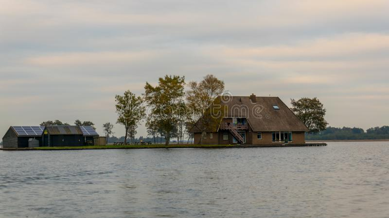 Uma casa em Giethoorn, nos Países Baixos, fotografados nos canais de água em um dia da queda, com grama verde, e arquitetura es fotografia de stock