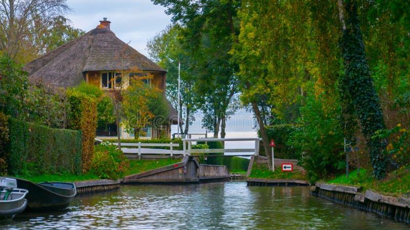 Uma casa em Giethoorn, nos Países Baixos, fotografados nos canais de água em um dia da queda, com grama verde, e arquitetura es imagens de stock