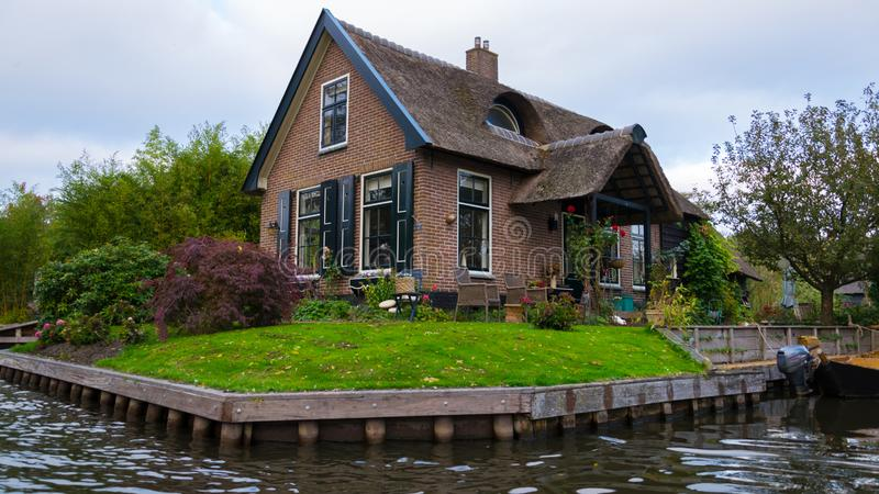 Uma casa em Giethoorn, nos Países Baixos, fotografados nos canais de água em um dia da queda, com grama verde, e arquitetura es imagem de stock royalty free