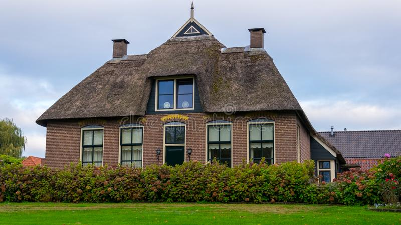 Uma casa em Giethoorn, nos Países Baixos, fotografados nos canais de água em um dia da queda, com grama verde, e arquitetura es fotografia de stock royalty free