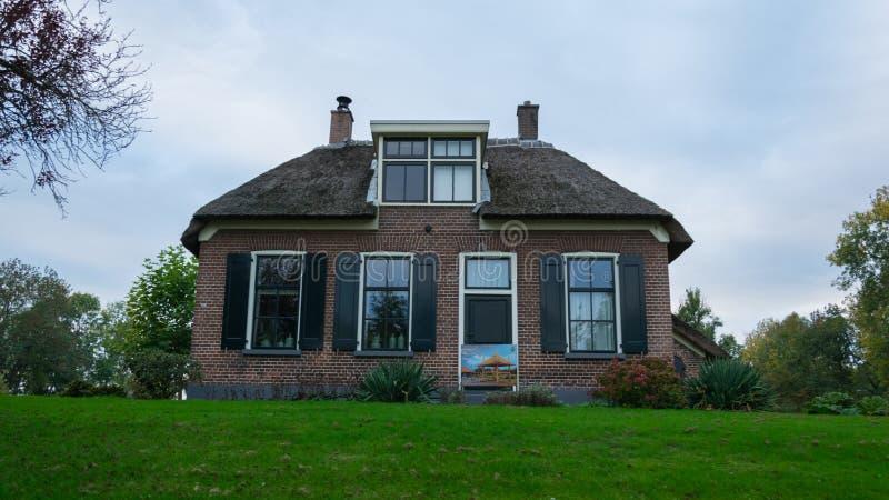 Uma casa em Giethoorn, nos Países Baixos, fotografados nos canais de água em um dia da queda, com grama verde, e arquitetura es foto de stock