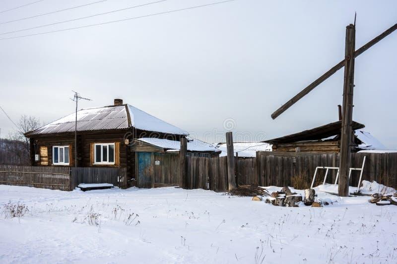 Uma casa ordinária de madeira em uma vila Siberian pequena na estação do inverno foto de stock