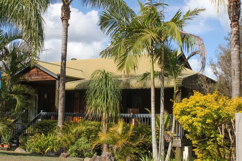 Uma casa rústica de Queensland construída da madeira natural com um telhado verde incomum da lata e encoberta na folha tropical imagens de stock