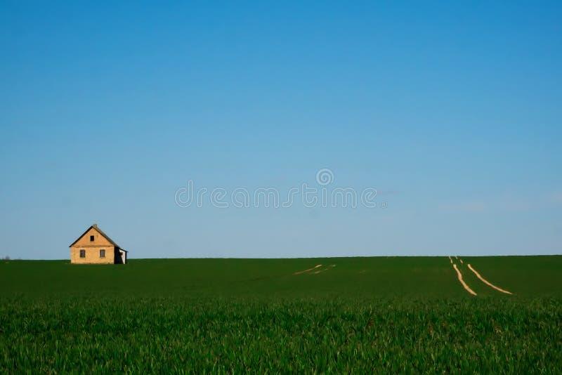 Uma casa só em um campo verde imagens de stock royalty free