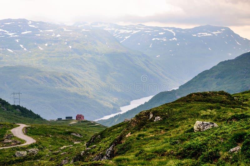 Uma casa vermelha pequena no horizonte acima do fiorde profundo e estreito em Noruega, Europa foto de stock royalty free